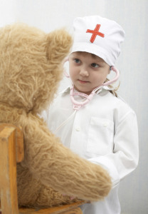 little girl playing doctor with teddy