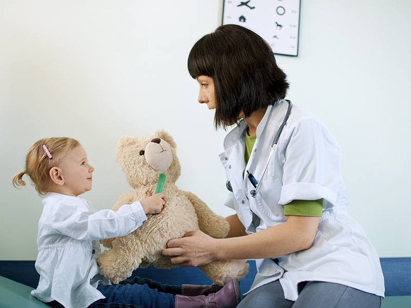 Paediatrician with child and teddy