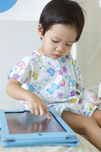 child in hospital with tablet device
