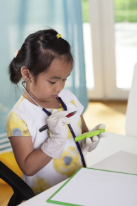 girl with notepad playing doctor